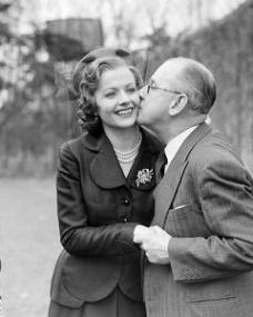 Herbert Wilcox gives Margaret Lockwood a peck on the cheek; wife Anna Neagle looks on.