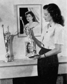 Margaret Lockwood stands in front of her chimneypeice and admires her Daily Mail Film Award