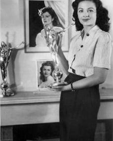 Margaret Lockwood stands in front of her chimneypiece and holds up her Daily Mail Film Award