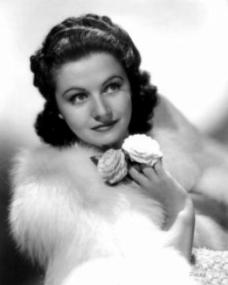 A young Margaret Lockwood delicately holds a pair of white roses