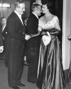 Margaret Lockwood in full-length evening gown and opera gloves shakes hands