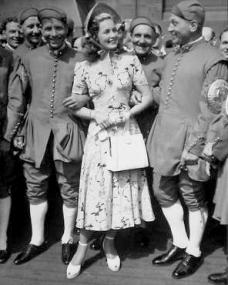 Patricia Roc is entertained by men in their national costume