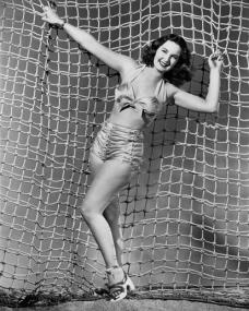 Patricia Roc in a bikini hangs from a net