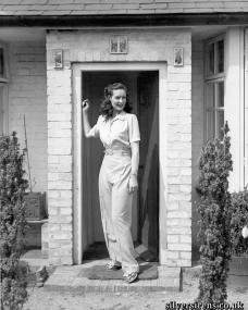 Patricia Roc stands on the steps of a brick porch.  The actress is dressed in a light-coloured trouser suit and sandals.