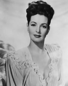 Patricia Roc wears a white dress with her hair up