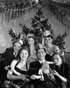 Some of the cast of Young Wives' Tale pose in front of a Christmas tree for the Picturegoer Christmas party on 13th December, 1950.  Present are (l-r) Derek Farr, Helen Cherry, Joan Greenwood, Richard Todd, Audrey Hepburn, and Phyllis Calvert