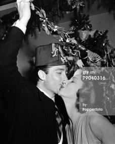 "Pictured kissing under the mistletoe are British actor Richard Todd and actress Joan Greenwood.  ""Picturegoer"" film stars Christmas Party, 1st January, 1950.  (Photo by Popperfoto/Getty Images)"