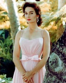 Beautiful Jean Simmons looks demure in a pink dress.   Behind her is sunny woodland.