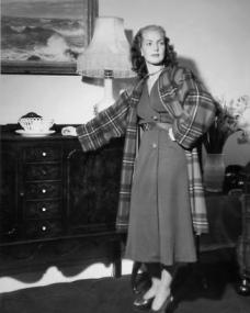 Patricia Roc wears a plaid overcoat as she leans against a dresser