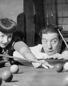 Sid Field looks mournful as he plays snooker with 1940s singer, Lind Joyce