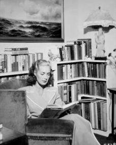 British film actress Patricia Roc reads at home in a comfortable armchair