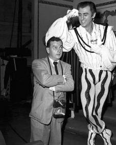 Stewart Granger in 1952 on the set of MGM's Scaramouche, for which he is in costume. Granger is seen here horsing around with the film's still photographer who is trying to get some good photos of the star