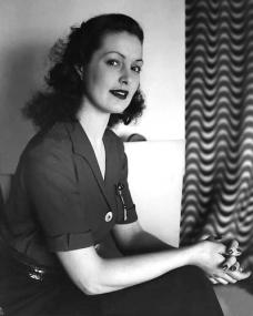Patricia Roc clasps together her hands as she wears a short-sleeved shirt