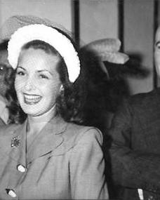 Patricia Roc smiles broadly in a lace hat