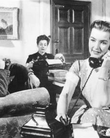 Captain Wilding (Anthony Steel) looks on as his wife Anne (Patricia Roc) takes another phone call as her secretarial business goes from strength to strength