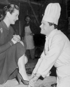 Patricia Roc and Anthony Steel enjoy a joke together on the set of Something Money Can't Buy.    In the film they play husband and wife and he owns a roving restaurant – hence the chef's clothes.  Something Money Can't Buy is a timely comedy of married life in post-war Britain.