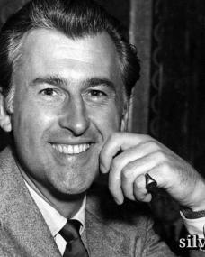 British actor Stewart Granger beams a smile at the camera in this candid shot.  Granger is dressed in a light jacket, dark tie and pale shirt; on his left little finger he wears a sovereign ring