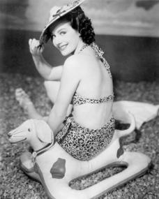 Margaret Lockwood sits on the beach in her swimming costume beach