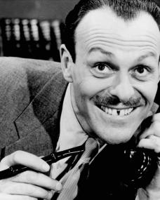 British actor Terry-Thomas holds a cheroot while on the telephone