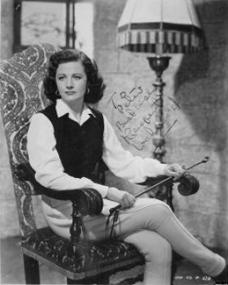 Margaret Lockwood holds a riding crop while she sits beneath a standard lamp in an armchair