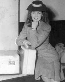 Patricia Roc poses with a couple of suitcases as she waits patiently for customs