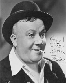 Autographed photo of English actor, Wally Patch (1). The actor wears a bowler hat and open-necked shirt, while a cigarette droops from his mouth