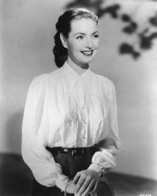 A happy Patricia Roc wears a white blouse