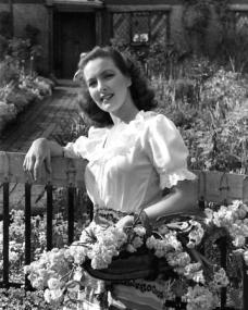 Patricia Roc in a white dress sits on a bench and relaxes in the garden