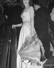 Patricia Roc in a formal white dress pauses to look back down the staircase