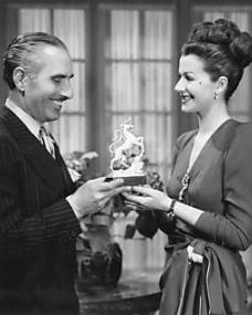 Margaret Lockwood being presented with a white unicorn statue by Harold Huth during the making of The White Unicorn