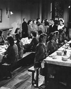 Lucy Glover (Margaret Lockwood) is warden of a remand home for girls. A new arrival, Lottie Smith (Joan Greenwood, seated left), has appointed herself ring leader of the girls and is rapping on the table with a spoon.    Lottie, product of the slums, has been remanded on a charge of attempting to murder her child and commit suicide herself.    Lucy wins her confidence and she tells the story of her life: she had a drunken father, a sluttish mother and five young brothers and sisters – all living in one room
