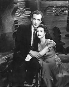 Dick (Dennis Price) asks Lucy (Margaret Lockwood) whether she regrets her divorce from Philip Templar (Ian Hunter), her former husband, and the separation from her child