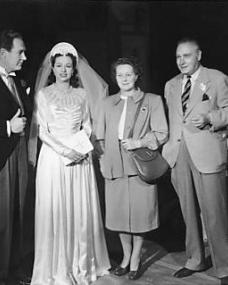 Two welcome visitors to Nettlefold studios were Chrissie White and Henry Edwards, stars of the silent days. They arrived for the wedding sequence in The White Unicorn and are seen chatting to present day stars of the film, Margaret Lockwood and Ian Hunter