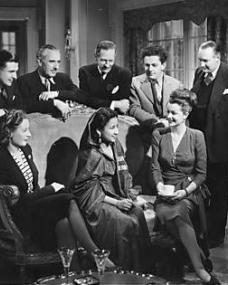 Miss Jayawardana, a Ceylonese visitor to Nettlefold Studios is entertained on set by (left to right) John Boxer, Harold Huth, Guy Middleton, Bernard Knowles (director), Reg Wyer (lighting cameraman); and seated, Eileen Peel and Margaret Lockwood