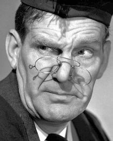 British character comedian, Will Hay, wears a mortar board in his trademark schoolmaster role