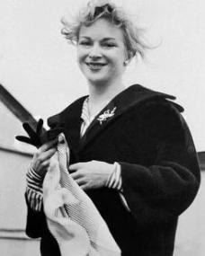 A windswept Joan Greenwood arrives on a BOAC flight to London Airport