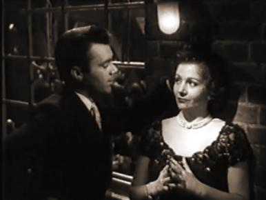 Mrs Jeffries (Margaret Lockwood) cooly listens to a proposition from Teddy (Dirk Bogarde), in a film clip from Cast a Dark Shadow