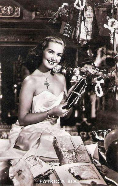 British actress Patricia Roc sits wears an off-the-shoulder dress as she sits in front of a real fire  Roc is surrounded by Christmas presents and decorations