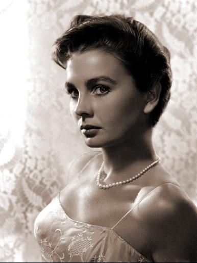 Jean simmons wears a pearl necklace and a lacy top