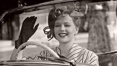 Georgette Constantin (Peggy Cummins) waves a hand behind the wheel of her car in the 1950 film, My Daughter Joy