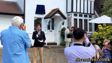 """Richard Williams, 1940s film buff and owner of """"Silver Sirens – The Golden Age of British Cinema"""" gives a speech about Margaret Lockwood at the unveiling of a commemorative blue plaque at 34, Upper Park Road, Kingston.  Actresses Julia Lockwood and Vicki Michelle watch from the front garden.  Saturday, 4th July, 2015"""
