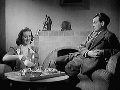 Joan (Patricia Roc) treats her brother Jim (David Farrar) to tea at home