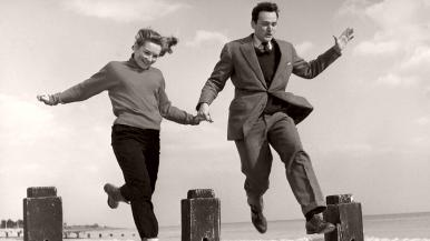 Anna (Odile Versois) and Ted (David Knight) and hold hands as they jump over groynes on a beach