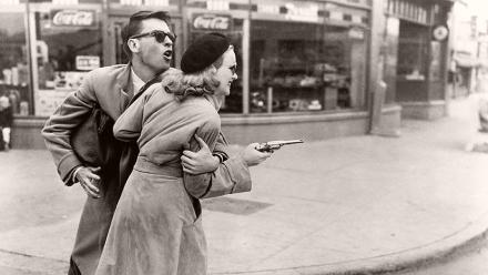 Barton Tare (John Dall) restrains an armed Annie Laurie Starr (Peggy Cummins) in the street.  Scene from the 1950 film Gun Crazy