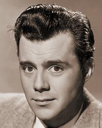 Signed photo of British actor, Dirk Bogarde.  The actor wears a jacket, jumper and tie, and sports a signet ring