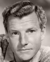 British actor Kenneth More wears an open-necked checked shirt and watch in a casual publicity photo