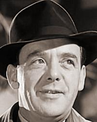 Grimshaw (Mervyn Johns) wears a hat and bow tie in My Learned Friend (1943)