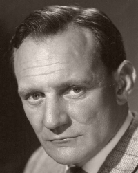 British actor Trevor Howard smokes a cigarette.  Howard is dressed in a herringbone jacket and tie