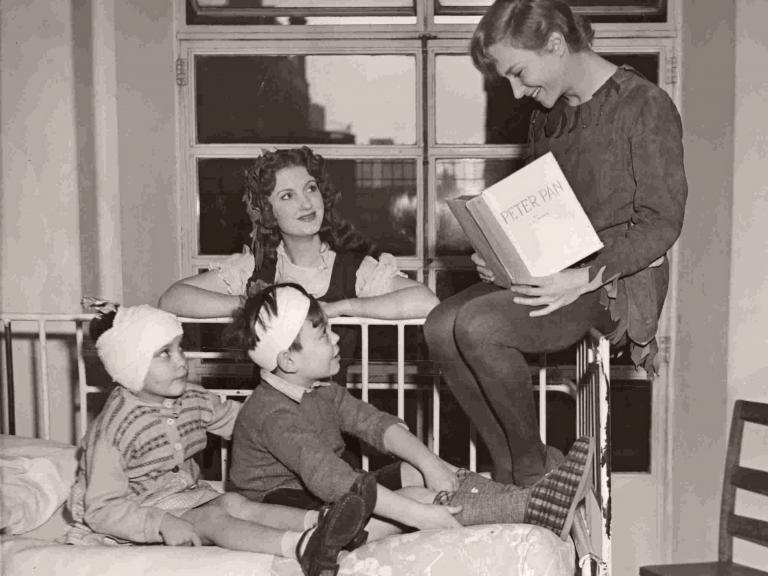 British actress Joan Greenwood, in costume as Peter Pan, sits on the end of a ward bed and reads to the sick children