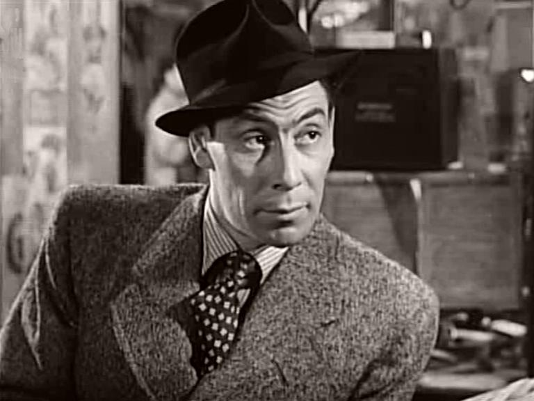 Lou (John Slater) in overcoat, tie and hat in a scene from It Always Rains on Sunday (1947)